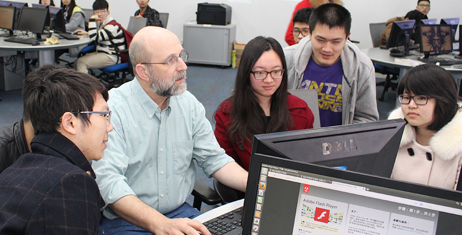 Students and professor working around computer