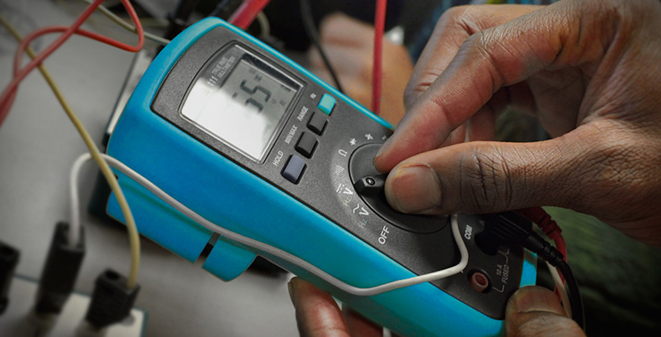 hands using a multimeter