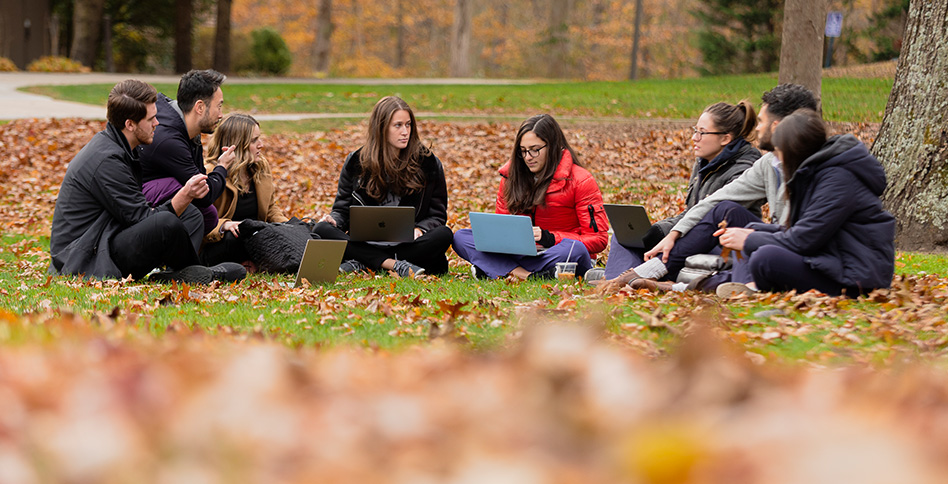 Students sitting in circle on ground outside using laptops