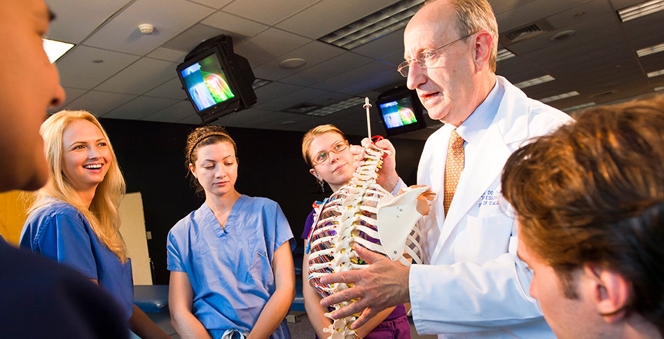 nyitcom instructor and students work with anatomical model